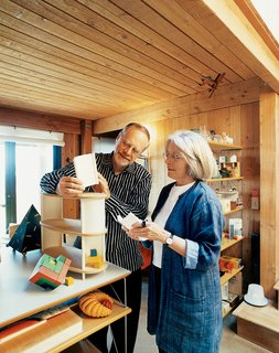 Partners in Design - Photo 1 of 10 - In the living room of their home at The Sea Ranch, Maynard Hale Lyndon and Lu Wendel Lyndon examine LyndonDesign's new shelving system. Next to the system sits Maynard's prized Cubicus by Peer Clahsen.