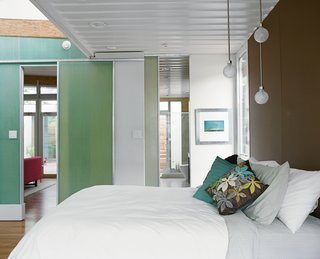 "The master bedroom is another place where Robertson placed emphasis on the existing size and shape of the containers. The room opens up to a clerestory window beyond the foot of the bed but the exposed edge of the container ceiling makes ""you almost feel like a hobo on a train,"" Feldmann says, romanticizing about her view from bed."