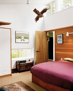 Cohen's bedroom is clipped onto one end of the house, just across from Sally's bedroom. A door to the left of the bed leads into his spacious bathroom, where he cleans up after long, muddy hikes in the woods with his golden retriever, Daisy.