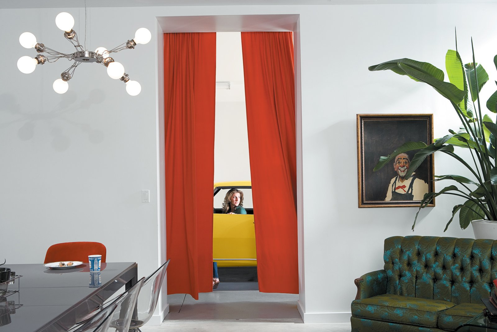 Living Room, Sofa, Pendant Lighting, Table, and Chair At the edge of the dining room, with its eclectic collection of fixtures and furnishings, orange velvet curtains playfully frame an opening to the skylight garage. It serves as a kind of sculpture gallery for motorcycles and cars, including one of Surratt's favorites, a yellow 1968 Camaro Rally Sport.  Photo 7 of 10 in The Brick Weave House in Chicago
