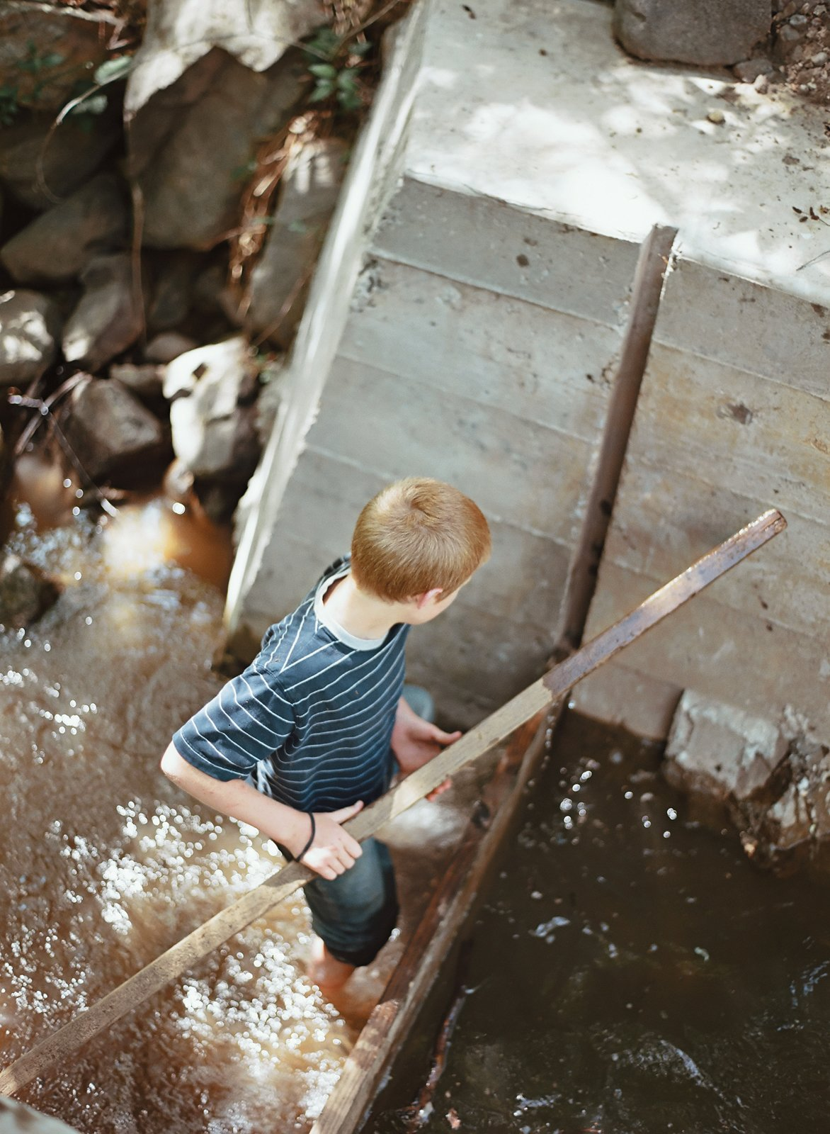 The young Meffans relish playing in the creek's adjustable dam, made from poured concrete. The nutrient-rich silt that collects over the summer is dumped on the vegetable garden in the winter, when the creek flows freely.  Photo 13 of 13 in Diamond in the Rough (and Ready)