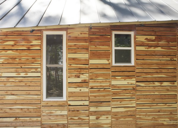 "The students also attempted to appease residents by making their home ""of the area."" They based the design on vernacular shotgun houses and bought the cedar siding as off-cuts from a local lumberyard, which totaled $120.<br><br>Photo by <br><br>Ty Cole"