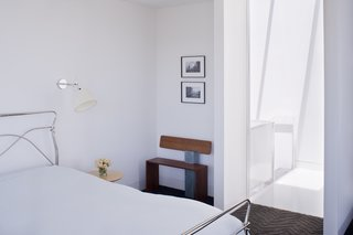 Back in the master bedroom, the designers installed Tolomeo wall sconces by Artemide next to the bed and placed a bench next to the door made by Hart's uncle, Peter Czuk of Czuk Studio. The bedroom door, which is rarely closed, is the starting point for the continuous flow of movement and light from the top of the house to the main level and down to the bottom floor.<br><br>Photo by <br><br>Sharon Risedorph
