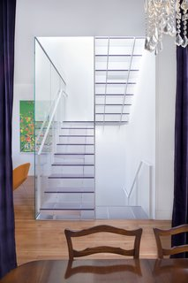 The view of the stairs from the dining room on the main floor highlights the stairwell's function as a lightwell. Samaha and Hart chose one-inch-thick Ecorsein by 3Form for the treads and risers, as it was the most transparent, scuff-resistent finish they could find. For the handrails, they used painted steel; for the center panel, a mix of acrylic and steel.<br><br>Photo by <br><br>Sharon Risedorph
