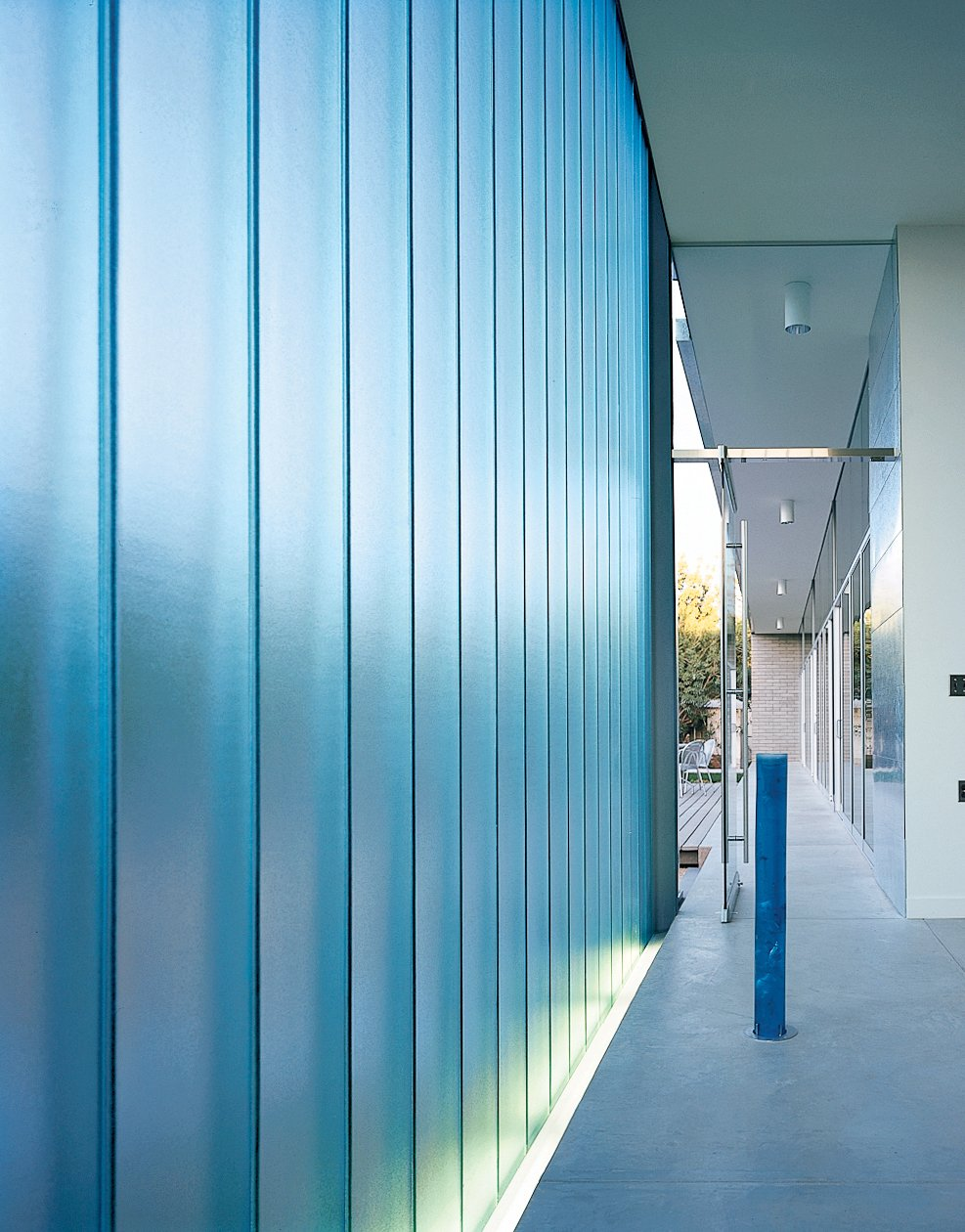 Walls of channel glass, an industrial material that comes in long strips shaped in a shallow U, help preserve the residents' privacy, while allowing only soft, filtered light inside. In the chapel, the DeBartolos paired and staggered the narrow panels so that only the most opaque light comes through. Obscure views and the most basic shapes and colors from outside create a glowing, ethereal quality indoors. Holy water is held in an elegant blue glass cylinder.  Photo 4 of 6 in Houses of the Holy