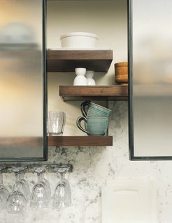 The Feld kitchen bridges eras by bringing together traditional designs and materials (the big Shaw's Original English farmhouse sink, fir floors, honed marble counters) with industrial designs. Open walnut shelving helps convey a sense of lightness. The pot-and-pan drawers pull out for easy access, while rolling steel-framed panels of textured glass above the counter act as a scrim, allowing the Felds to choose what to obscure and what to display.