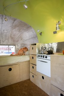 In this Airstream renovation, the owner was intent on keeping the original stove and incorporating it into the cabinetry. He created a backsplash using inexpensive aluminum flashing that he texturized with a ball pein hammer.