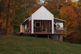 Red and yellow accent colors blend with natural North Carolina foliage. Cantilevered porches and decks provide deep shadows. Image courtesy Chad Everhart Architect.