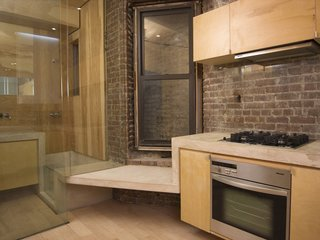 The kitchen has a Miele cooktop, oven and hood, as well as a small seat before a double-hung window, one of very few natural light sources in the apartment. The concrete ribbon continues into the adjacent bathroom, becoming part of the bathtub and counter. Image courtesy Brian Riley.