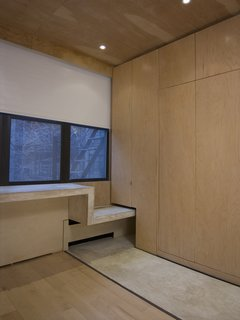 Floor-to-ceiling maple sheathes the storage cabinets and the bottom of the Murphy bed, at right. The concrete ribbon continues as a window seat before becoming a desk.