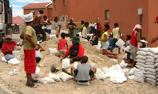Mpahlwa took inspiration from the vernacular architecture of his youth in a rural part of the Eastern Cape, where people built homes from mud, water, and timber, to transform what is generally considered a nuisance—the abundance of sand—into an invaluable resource for holding down a house. Members of the community, seen here, gathered together to pack bags full of sand. Image courtesy Interactive Africa/ Design Indaba