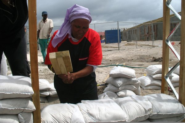 Luyanda Mpahlwa - Photo 4 of 9 - Once the frame of the house was constructed, the townspeople filled the wall space with sandbags. Here, Olga Jonkers uses a handmade tool to compact the bags that will become the walls of her future home. Image courtesy Interactive Africa/ Design Indaba