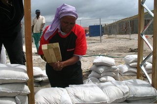 Once the frame of the house was constructed, the townspeople filled the wall space with sandbags. Here, Olga Jonkers uses a handmade tool to compact the bags that will become the walls of her future home. Image courtesy Interactive Africa/ Design Indaba