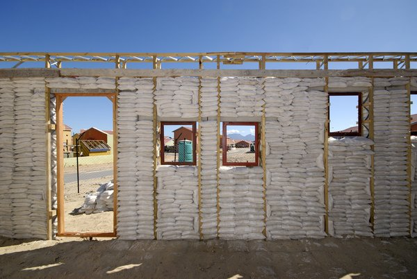 After the walls of the first-floor frames were filled tightly with sandbags, the workers plastered wire mesh onto the exterior. Image courtesy Interactive Africa/ Design Indaba