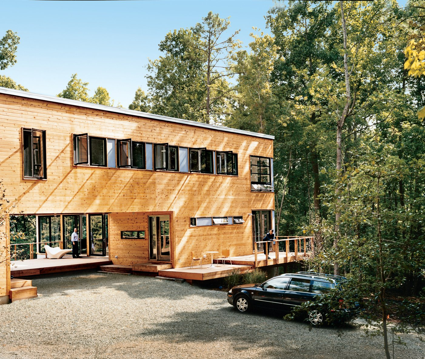 Wieler and Tung enjoy two of the home's several decks.The home is clad in red cedar siding and features a multitude of view-enhancing windows by Loewen. The decking is composite wood by Trex.  Photo 1 of 12 in Prefab, Proven