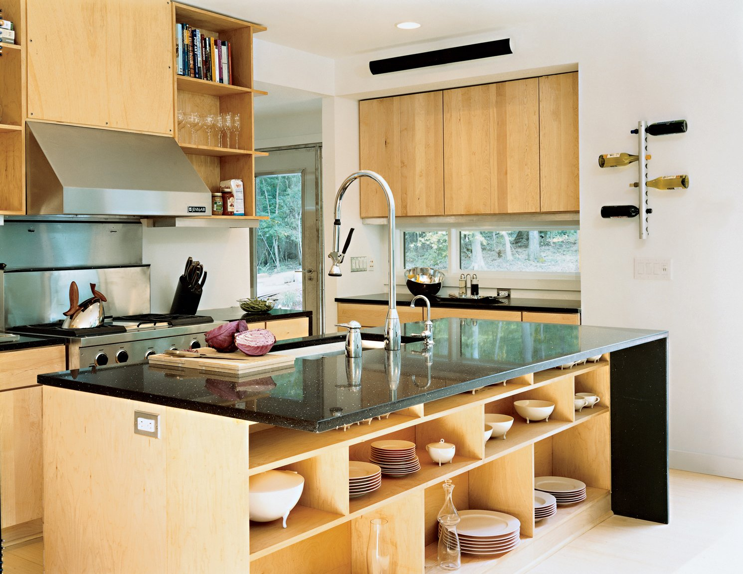 Wieler and Tung wanted a space conducive to entertaining, and this open kitchen delivers. It features a stainless steel refrigerator, Pro-Style gas range, hood, backsplash, and two-rack tub dishwasher, all from Jenn-Air. The ebony countertop, which allows the chef to interact easily with guests, is from Caesarstone. The distinctive faucet and Poise kitchen sink are from Kohler. Maple cabinets by Merillat (installed flush with the wall to save space and look sleek) provide ample storage space for all kitchen essentials. The under-counter storage space holds Victoria china  designed by Oscar Tusquets for Driade. The bread board was designed by Antonio Citterio for Iittala's Tools collection. The wine rack and oil/vinegar cruets are from Rosendahl.  Photo 7 of 12 in Prefab, Proven