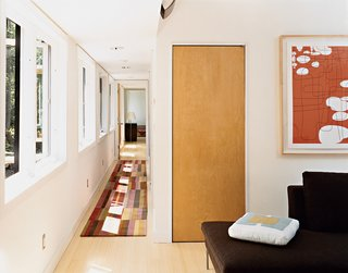 A view from the top of the stairs, past the office to the master bedroom. Sunlight filters through extensive fenestration to the hall, which features a runner by Emma Gardner. Artwork by Campbell Laird hangs over B&B Italia seating in the couple's office. Not shown is a Herman Miller desk complete with Aeron work chair.