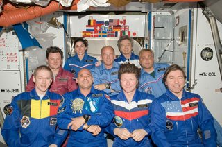Crew members on the ISS pose for a group photo following a joint crew news conference in the Harmony node of the International Space Station. Pictured from the left (front row) are European Space Agency astronaut Frank De Winne, Expedition 20 flight engineer and Expedition 21 commander; spaceflight participant Guy Laliberte; Russian cosmonaut Gennady Padalka, Expedition 19/20 commander; and NASA astronaut Michael Barratt, Expedition 19/20 flight engineer. From the left (middle row) are Russian cosmonaut Roman Romanenko, Expedition 20/21 flight engineer; NASA astronaut Jeffrey Williams, Expedition 21 flight engineer and Expedition 22 commander; and Russian cosmonaut Maxim Suraev, Expedition 21/22 flight engineer. Pictured on the back row are NASA astronaut Nicole Stott and Canadian Space Agency astronaut Robert Thirsk, both Expedition 20/21 flight engineers. Photo taken October 5, 2009. Image courtesy of NASA.