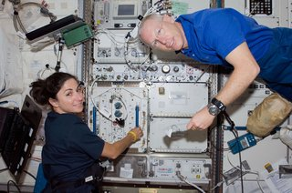 Astronauts Nicole Stott, Expedition 20 flight engineer; and Patrick Forrester, STS-128 mission specialist, work in the Kibo laboratory of the ISS while Space Shuttle Discovery remains docked to the station. Photo taken August 31, 2009. Image courtesy of NASA.