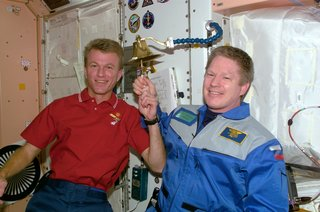 Astronauts Brent W. Jett, Jr. (left) and William M. Shepherd participate in an old Navy tradition of ringing a bell to announce the arrival or departure of someone to a ship. The bell is mounted on the wall in the Unity node of the ISS. The bell-ringing took place shortly after an in-space reunion on STS-97 Flight Day 9. Photo taken December 8, 2000. Image courtesy of NASA.