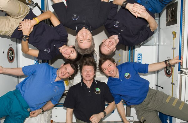 Expedition 20 crew members pose for an in-flight crew photo in the Harmony node of the ISS. Pictured clockwise are Russian cosmonaut Gennady Padalka (bottom center), commander; Russian cosmonaut Roman Romanenko, NASA astronaut Nicole Stott, Canadian Space Agency astronaut Robert Thirsk, European Space Agency astronaut Frank De Winne and NASA astronaut Michael Barratt, all flight engineers. Photo taken October 1, 2009. Image courtesy of NASA.