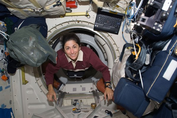 Astronaut Nicole Stott, STS-128 mission specialist, floats through a hatch on the Space Shuttle Discovery during flight day three activities. Photo taken August 30, 2009. Image courtesy of NASA.