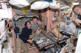 NASA astronaut Nicole Stott and Russian cosmonaut Roman Romanenko, both Expedition 20/21 flight engineers, are pictured at the galley in the Unity node of the ISS. Canadian Space Agency astronaut Robert Thirsk, Expedition 20/21 flight engineer, is mostly out of frame at right. Photo taken October 5, 2009. Image courtesy of NASA.