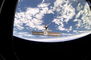 As seen through a window on Endeavour's aft flight deck, the ISS, then staffed with its fourth three-person crew, is contrasted against Earth's horizon during a farewell look from the shuttle following undocking. Photo taken December 15, 2001. Image courtesy of NASA.