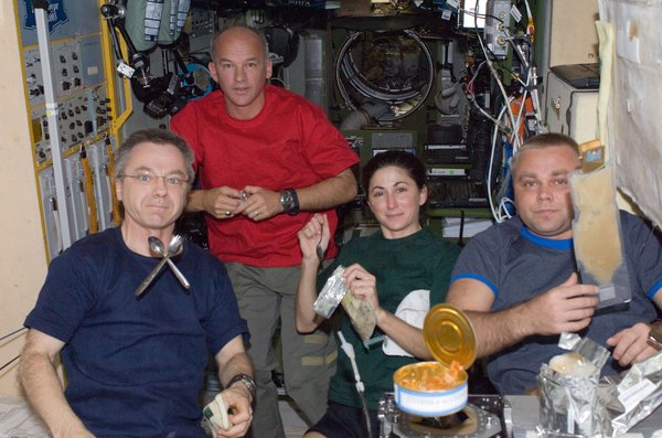 Canadian Space Agency astronaut Robert Thirsk (left), NASA astronauts Jeffrey Williams and Nicole Stott; along with Russian cosmonaut Maxim Suraev, all Expedition 21 flight engineers, share a meal at the galley in the Zvezda Service Module of the ISS. Photo taken October 12, 2009. Image courtesy of NASA.