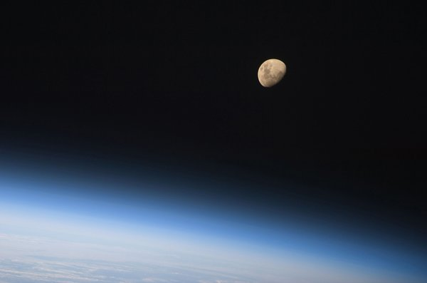 A gibbous moon is visible above Earth's atmosphere, photographed by an STS-128 crew member on the Space Shuttle Discovery during flight day three activities. Photo taken August 30, 2009. Image courtesy of NASA.