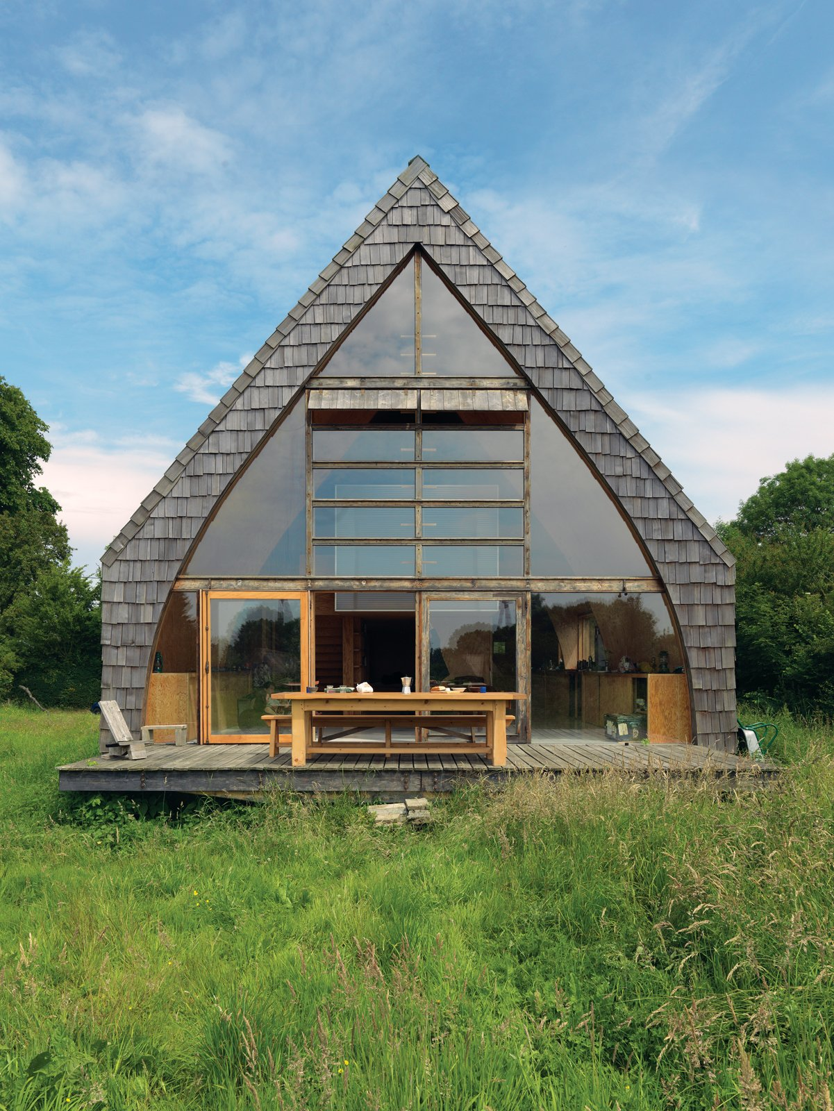 """Exterior, Cabin Building Type, House Building Type, A-Frame RoofLine, Shingles Roof Material, and Wood Siding Material """"I didn't want the kind of manicured garden that would mean I'd have to come out on weekends and mow the lawn,"""" says Jean-Baptiste Barache of the country home he built, mostly by himself, over a year and a half.  Photo 1 of 11 in Modern Wooden A-Frame Retreat in France"""