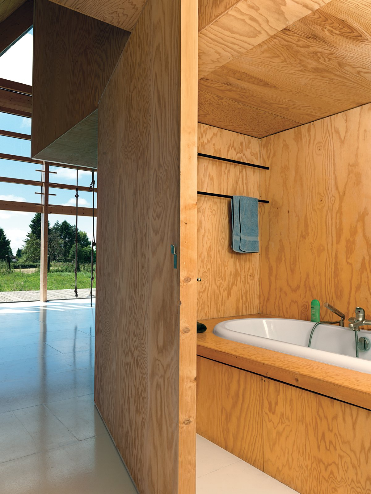 Bath Room and Drop In Tub Cubic bookshelves do double duty as a dividing wall and as a sliding door opening up to a hidden bath.  Photo 3 of 11 in Modern Wooden A-Frame Retreat in France