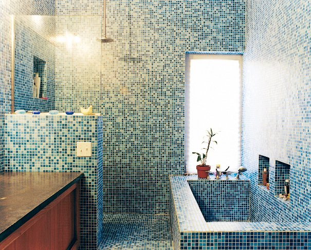 Bath Room, Granite Counter, Freestanding Tub, Soaking Tub, Ceramic Tile Floor, Open Shower, and Ceramic Tile Wall The blue-tiled master bathroom stands in contrast to the muted tones of the rest of the house. The tile is recycled glass from China.  Photo 6 of 9 in 9 Unusual Modern Bathrooms from The Family Tree