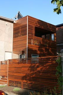 The architect used horizontal slats for privacy, but alternated them on the fence and second-floor deck to allow sunlight and breezes through. Solar panels atop the roof heat the water; a green roof is in the process of growing in. The project was awarded Green Renovation of the Year and Best Housing Detail at the 2009 Ottawa Housing Design Awards.