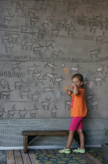 """Engraved House - Photo 12 of 17 - The couple's daughter, Kalyna, puts her own spin on her father's engravings, which he calls a """"concrete coloring book."""" Dedicating this side of the building to the earth, he carved herds of caribou into the panels. The abstract marks at the base skirt the entire exterior and were added for a consistent design element."""
