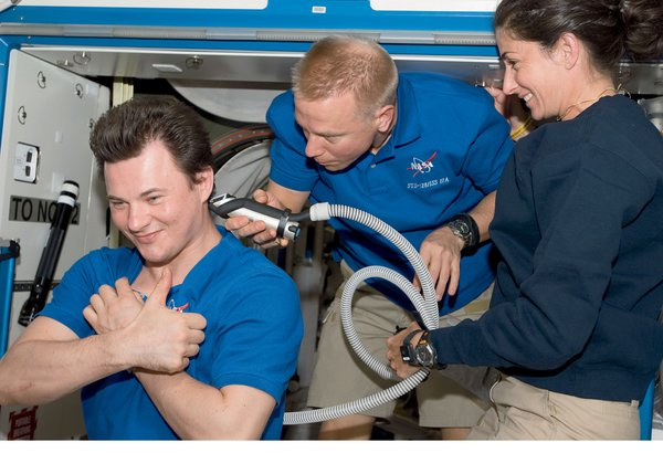 A haircut, performed by Tim Kopra for Roman Romanesko, calls for clippers connected to a vacuum to entrap cut hair. Image courtesy of NASA.