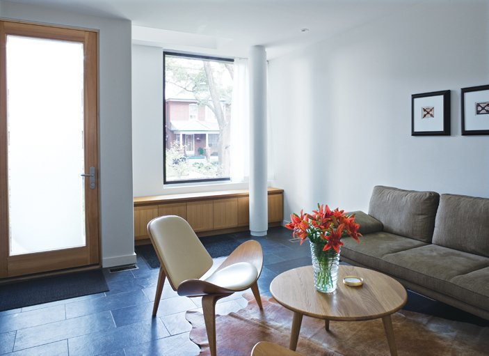 Living Room, Chair, Sofa, Coffee Tables, and Rug Floor Just through the front door is the living room where built-ins by Chong share space with a three-legged Wegner chair and photographs by Arnaud Maggs.  Photo 1 of 18 in Narrow Modernist Three-Story Home in Toronto