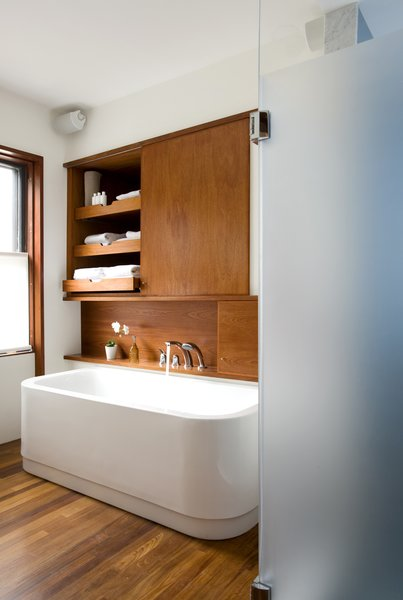 """The leftmost cabinet above the Duravit bathtub (equipped with KWC fixtures) occupies the space where a doorway once lead into the living room, creating unnecessary traffic from the home's public spaces through to the master bedroom. The new bathroom features a minimal palette of white and teak. """"It's able to hold up on boat decks so is good for a bathroom,"""" Klug says. It also makes the heated floor that much nicer to walk on in the morning."""