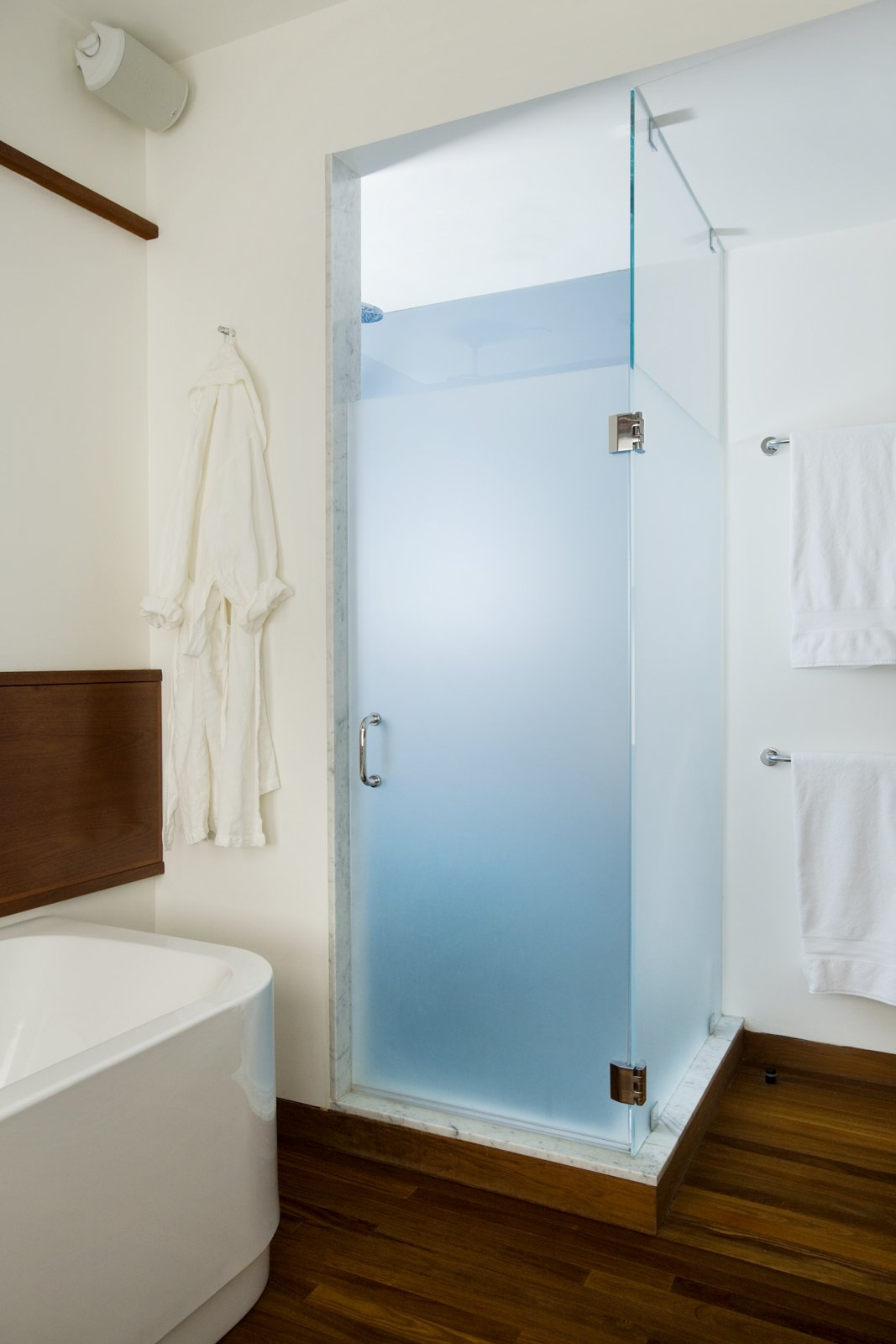 The shower is one corner of the renovated bathroom and adds a slash of color—a blue to match the color of the Aegean Sea as the homeowner remembered it after a trip to the Mediterranean.Butz and Klug chose towels bars and accessories from   Dornbracht to finish the room's look.Photo by   Eric Roth  Photo 4 of 4 in Loo & Improved