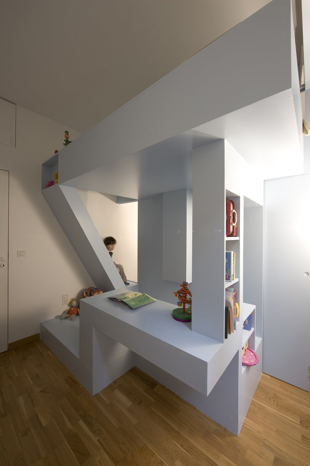 The bed seems to soar above the playing space, held up by bookshelf columns and a carefully angled staircase.  Photo 1 of 11 in Kids' Room Renovation