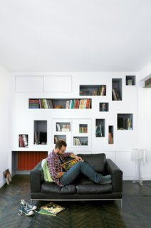 Shelf Life - Photo 1 of 27 - Mathieu Vinciguerra reads in front of his apartment's signature storyboard shelves.