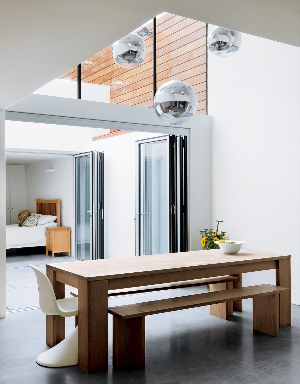 Dining Room, Pendant Lighting, Table, and Chair With the sliding doors open, the kitchen connects to a courtyard and spare bedroom, where friends who come over for dinner sometimes take up residence for days.  Photo 3 of 10 in Composite Index