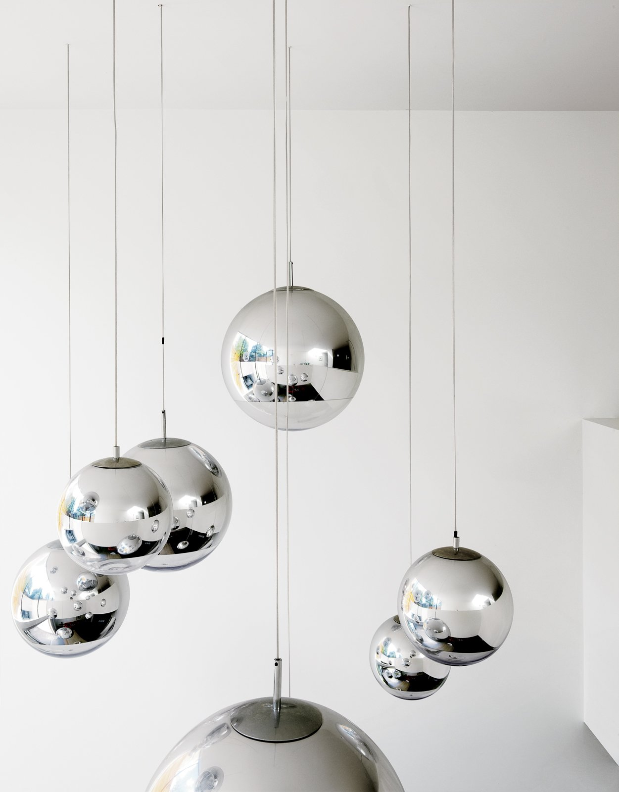 """Bruce worried about what to put in the double-height space above the kitchen table—–until he found these Tom Dixon–designed mirror balls. """"They were installed at random and when William came over that evening, he said, 'Fantastic, well done.' So we left them like that.""""  Photo 14 of 19 in How to Take a Dwell Photo"""