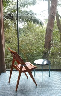 Her folding side chair, against the floor-to-ceiling window wall of the Glass House. Photo courtesy Espasso.