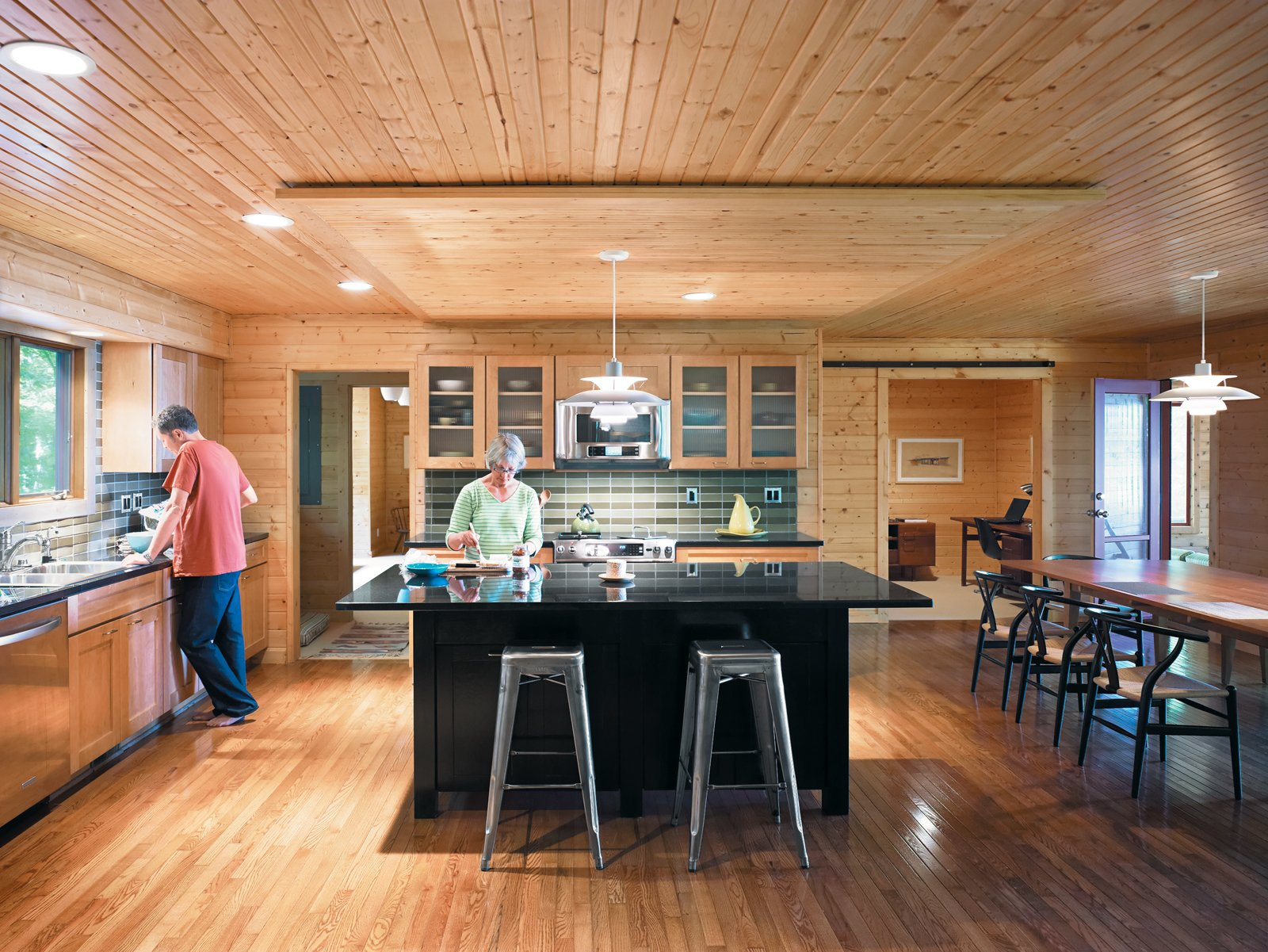 In the kitchen, Danish PH 5 lamps illuminate the island and table. The lined wood planks on both the ceiling and floor draw the eye naturally through the space to the study beyond, where Keith's father's original Jens Risom desk resides.  Photo 10 of 12 in Campbells' Coup