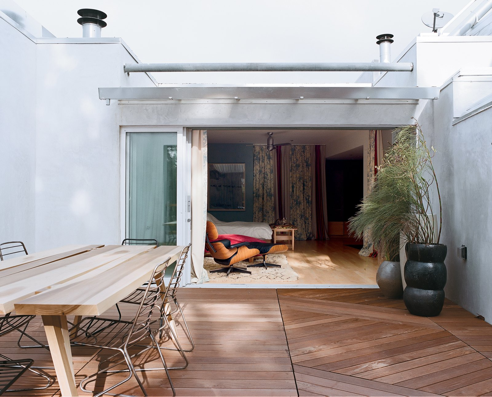 The bedroom flows into the new ipe deck, which houses a poplar table by Mike and Maaike and Drake chairs by One & Co, from Council Design.  Photo 13 of 14 in Project Runaway