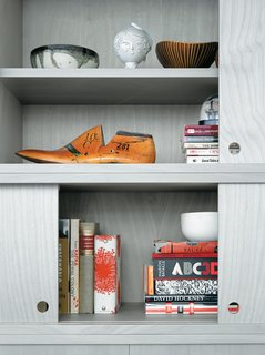 The cabinet doors of the living room wall unit, in birch veneer painted a calming gray, slide with silken ease but never fully close, leaving strategic gaps for the display of Jun's eclectic array of books and objects.