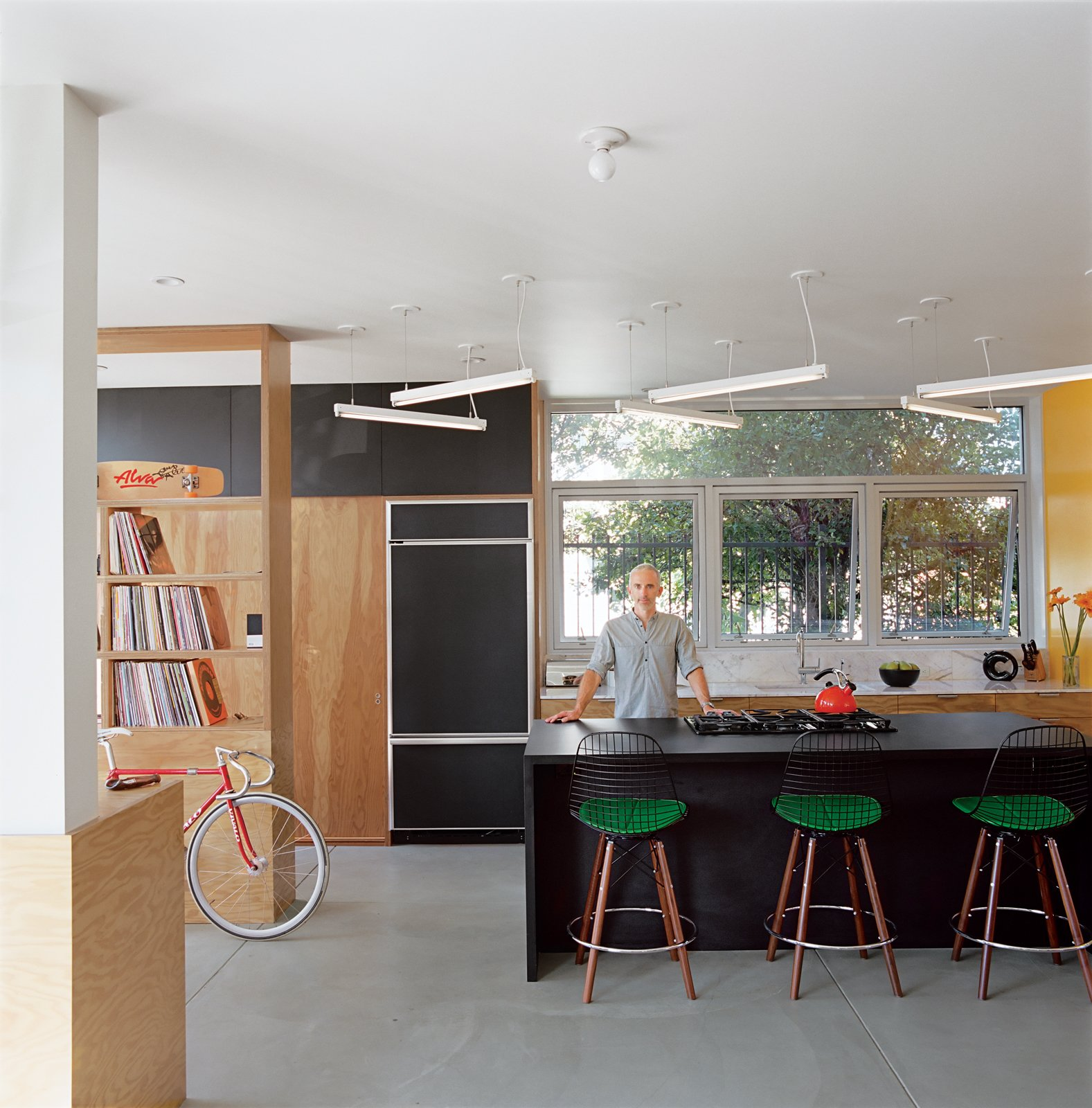 "The ""murdered kitchen"" includes a fluorescent light sculpture with dimmable ballasts designed by Bestor. The rough plywood offers a nice chromatic contrast.  Photo 5 of 11 in Daft Punk Could Play at This House"