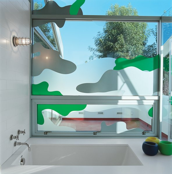 """Los Angeles–based graphic designer Chris Loomis created a trio of window decals for the house's three bathrooms. Grunbaum went with a camouflage pattern for privacy in the master bathroom, which has a wall of floor-to-ceiling glass that looks onto an adjacent patio. """"Because we're sort of in the trees, I wanted to keep the plant theme going,"""" he says. laloomis.com"""