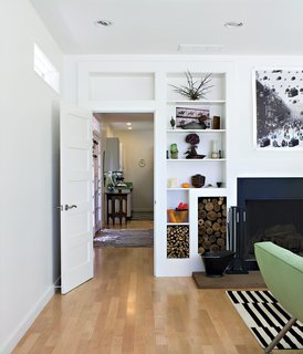 Ewing used Canadian maple for the hallway and living-room floors, giving them a bright, clean look. A built-in shelving system borders the hearth, creating functional and decorative storage spaces for firewood collected on-site.